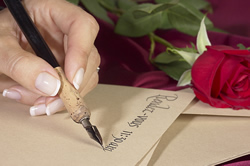 hand writing an invitation with a pen